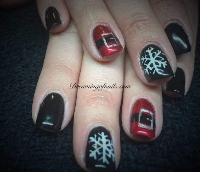 Black and red nails with painted snowflakes and Santa belts