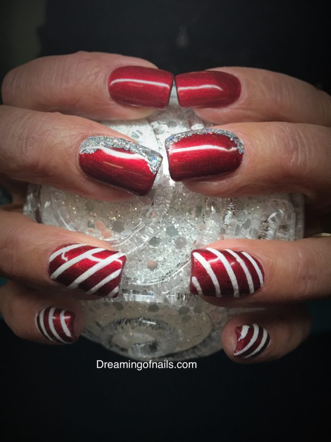 Red and white striped nails with silver glitter accents