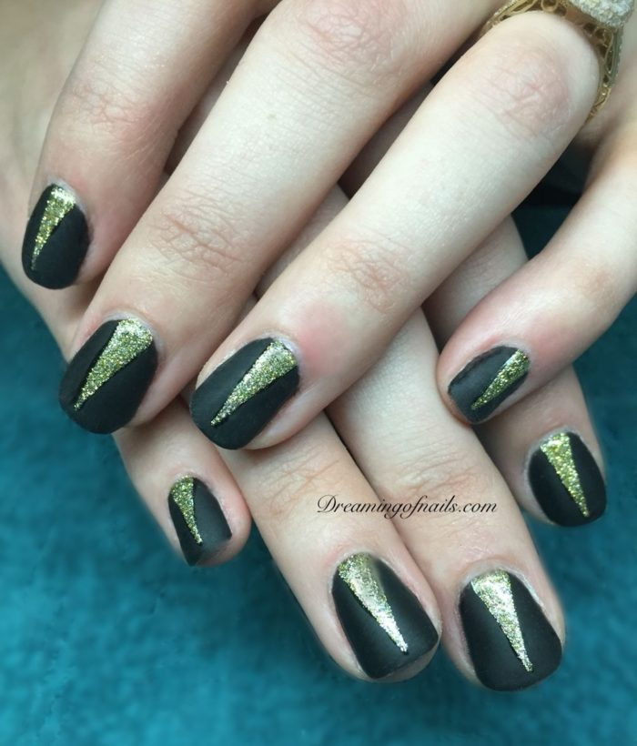 Black matte nails with gold glitter design