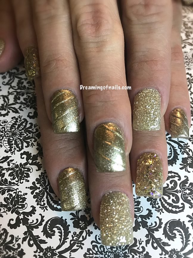 Gold metallic nails with gold glitter accents