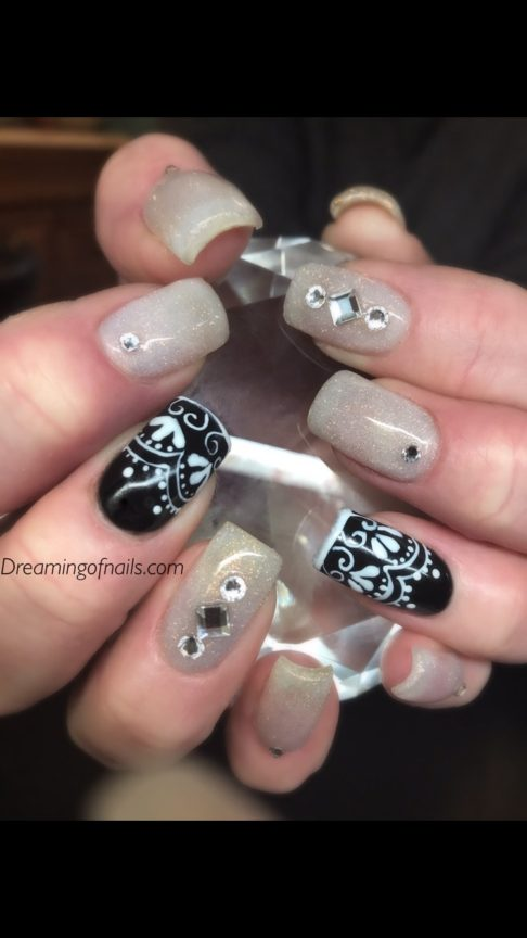 Shimmer nails with black and white painted designs and rhinestones