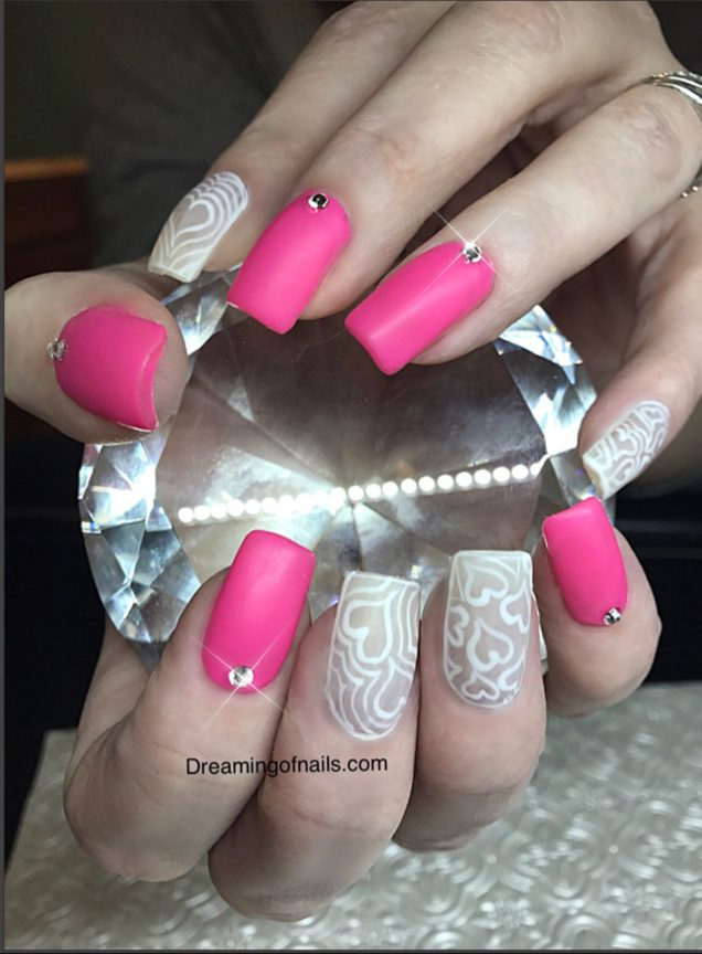 Pink matte nails with white heart designs and Swarovski crystals